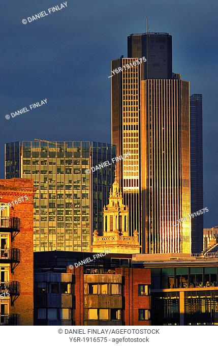 Buildings in the City of London financial district lit up by some unexpectedly bright sunhine bursting through the dark clouds of a miserable Winter evening at...