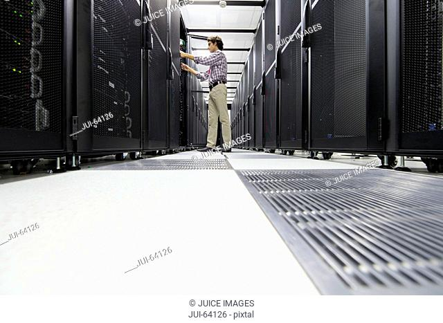 Technician working on server rack in data center