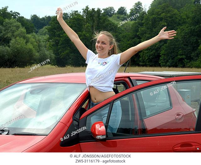 Young woman, 25 years old, stand smiling at a car and rising her arms on a country road in Scania, Sweden, Europe