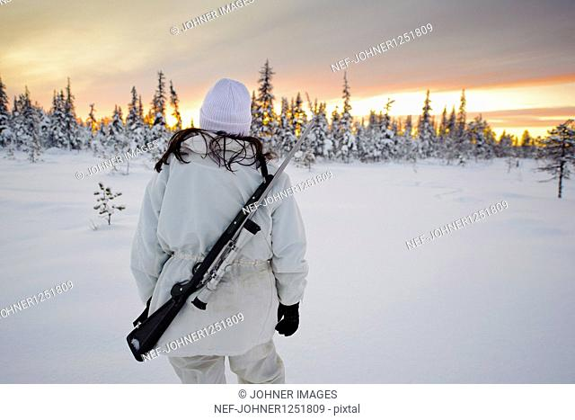 A woman with a sportinggun from behind