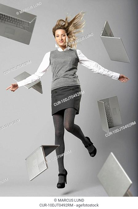 young business woman jumping with flying laptop computers
