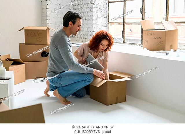 Couple moving into industrial style apartment, unpacking box