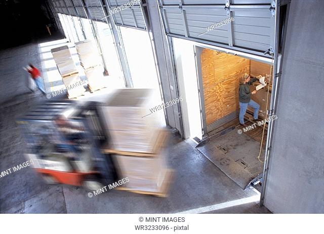 Employees loading cardboard boxes of products into truck trailers in a distribution warehouse loading dock area, one checking a manifest