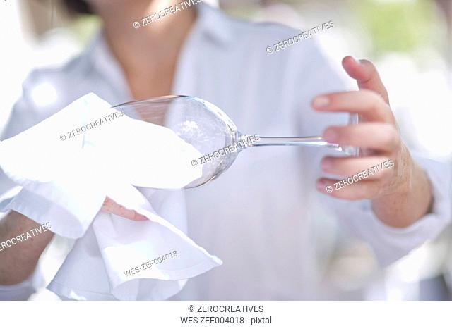Waitress cleaning a wine glass with a cloth