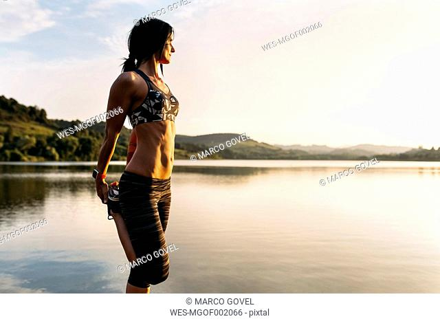 Female athlete stretching at the sea at sunset