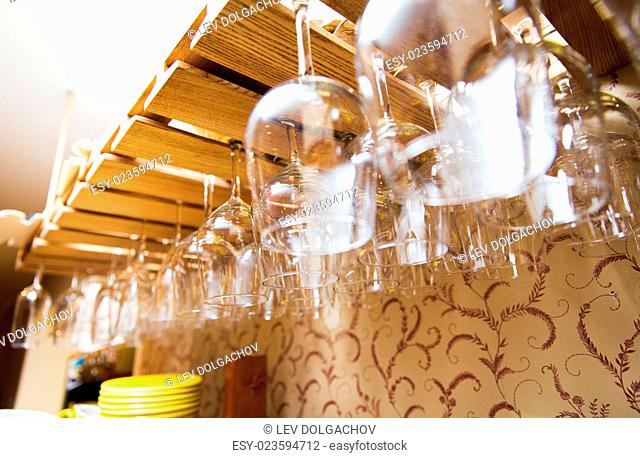 glassware, dishware and objects concept - wine glasses hanging upside down on bar holder