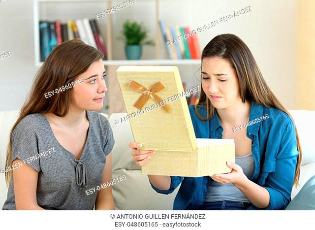 Disappointed girl opening a gift beside her friend sitting on a couch in the living room at home