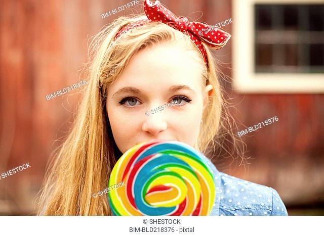Caucasian teenage girl licking lollipop