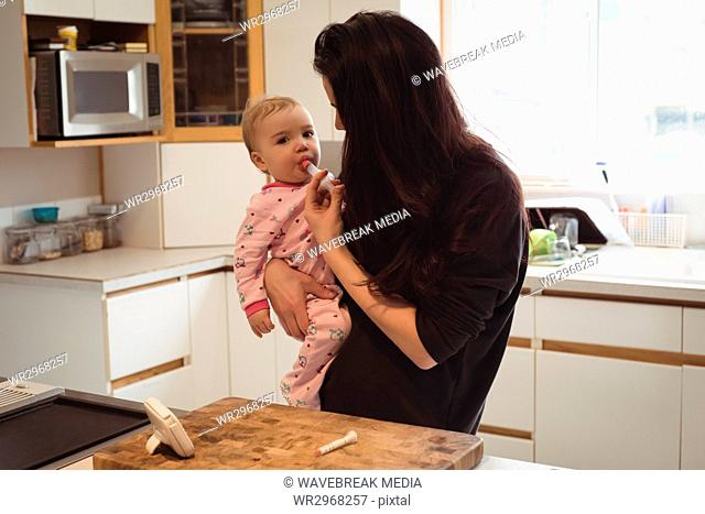 Mother feeding medicine to baby in kitchen