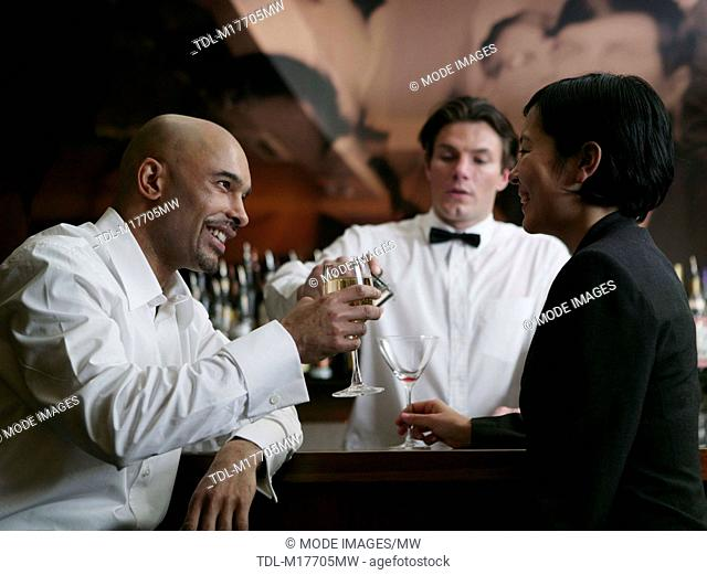 A young man and woman sitting at a bar together drinking