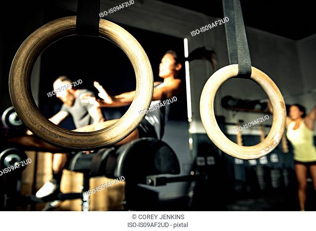 Close up of gymnasium rings with people training in background