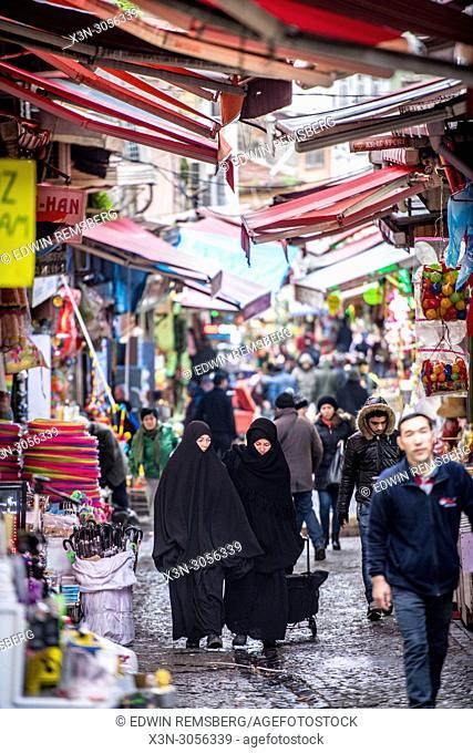 Two women wearing chadors walk along narrow street under awnings in outdoor market , Istanbul, Turkey