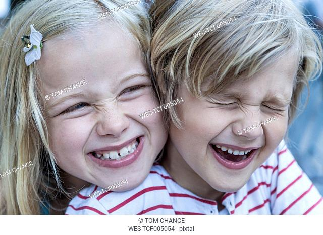 Portrait of laughing little boy and his sister head to head