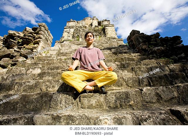 Asian woman meditating on temple ruins