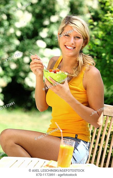 woman sitting in the garden eating salad