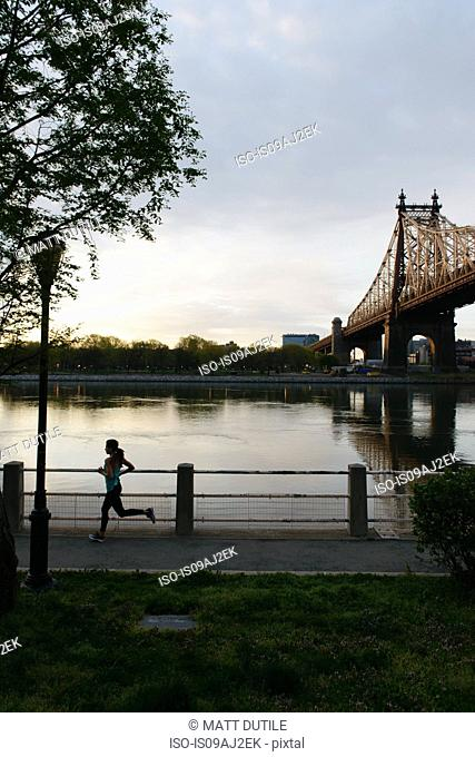 Silhouette of young woman running on waterfront, Roosevelt Island, New York City, USA