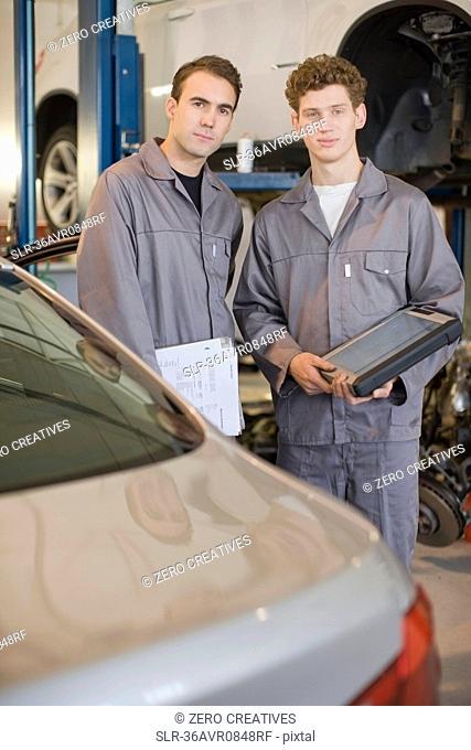 Mechanics examining cars in garage