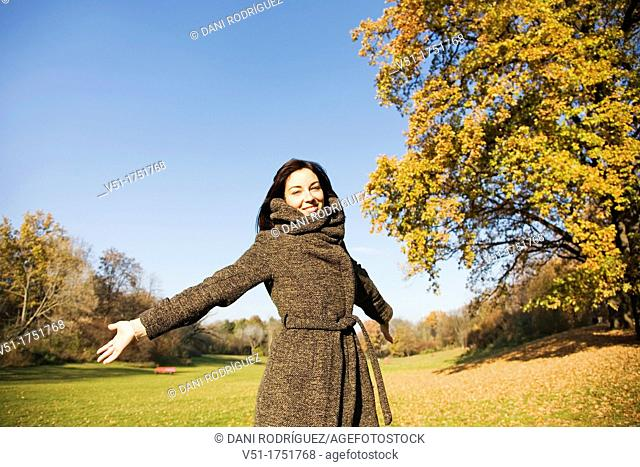 Portrait of a brunette beautiful woman with arms opened in park in Autumn