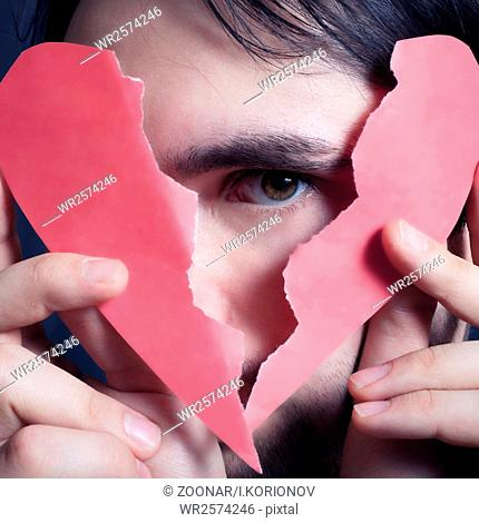 Face of young handsome man with broken paper heart
