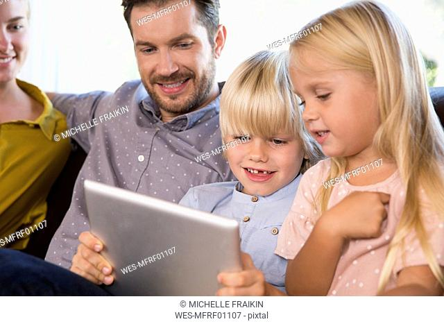 Family sitting on couch at home using tablet