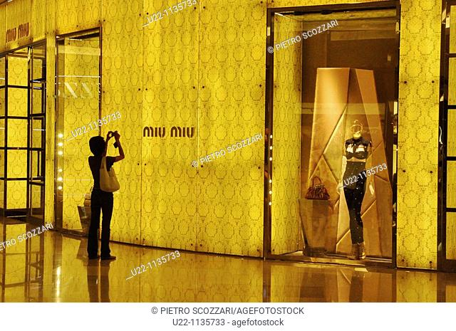 Singapore: a woman taking a photo of a shop in a mall along Orchard Road