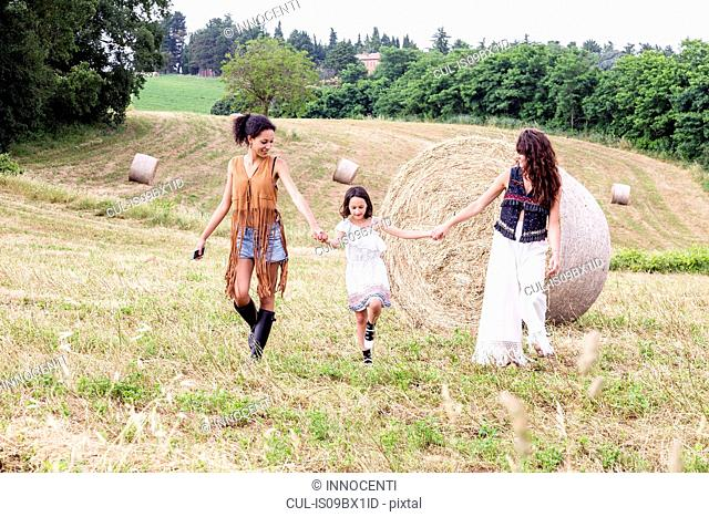 Friends and girl in field of hay bales, Città della Pieve, Umbria, Italy