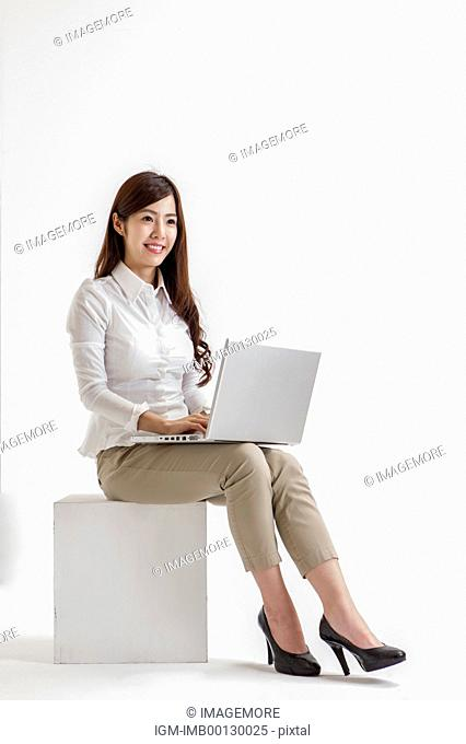 Young woman sitting and using laptop with smile