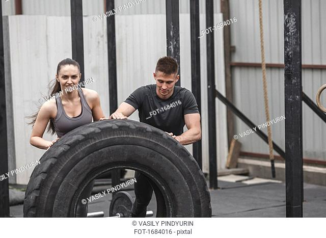 Male instructor assisting female athlete in flipping tire during crossfit training