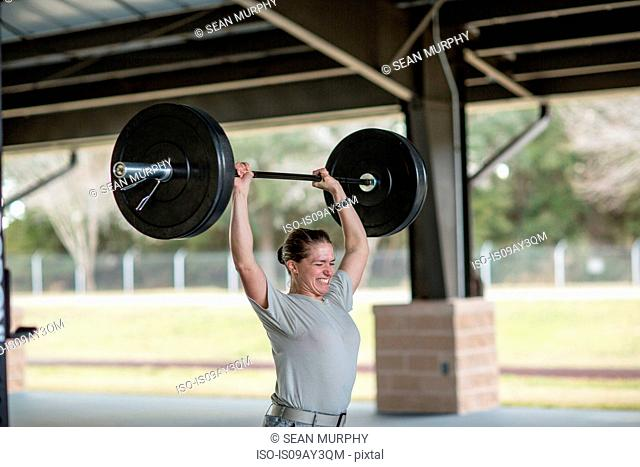 Determined female soldier lifting barbell at military air force base