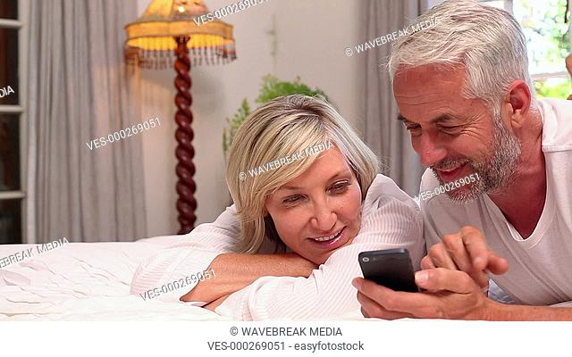 Couple lying on bed using smartphone together
