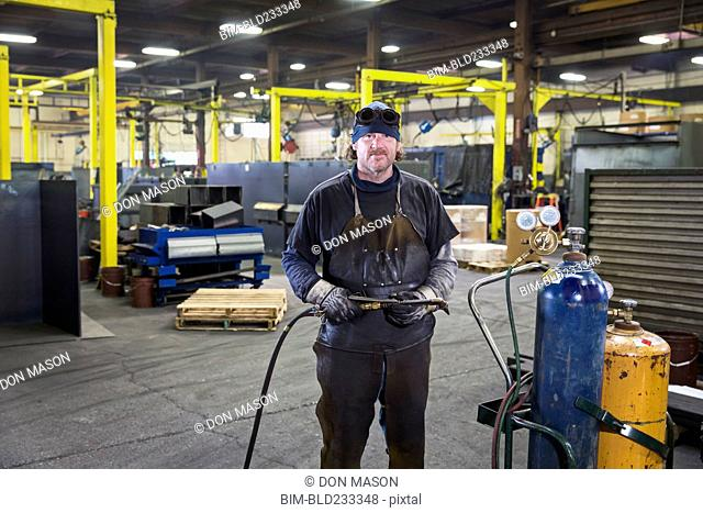 Caucasian welder posing with blowtorch in factory