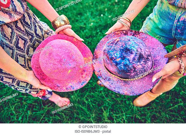 Waist down view of two young women holding felt hats covered in coloured chalk at festival