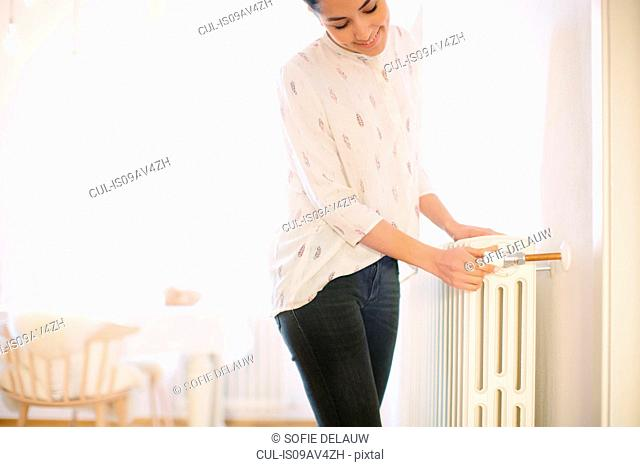 Young woman adjusting radiator switch at home