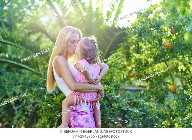 mother kissing daughter outside in nature garden. Australian ethnicity. During holiday stay in Hersonissos, Crete, Greece