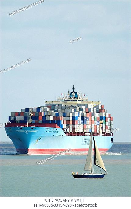 Container ship, fully loaded with containers, approaching docks, sailing boat in foreground, Felixstowe Docks, Suffolk, England