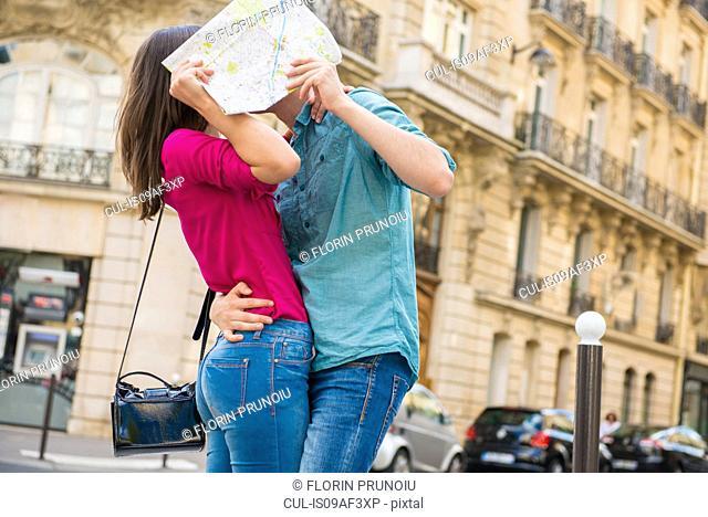 Young couple hiding behind map, Paris, France
