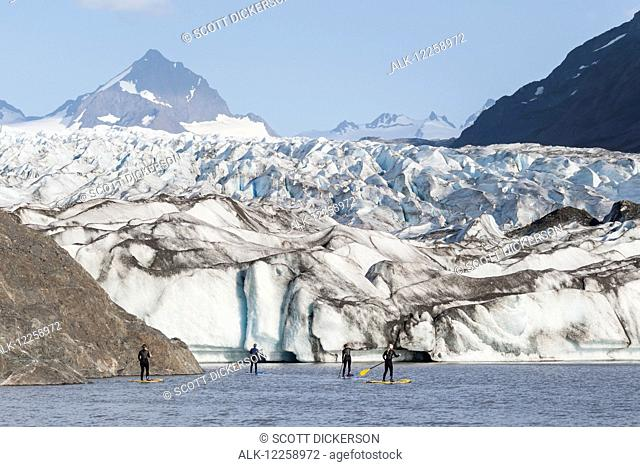 Standup paddleboarders paddling on flatwater with the Grewingk glacier in the background, Kachemak Bay State Park, Southcentral Alaska