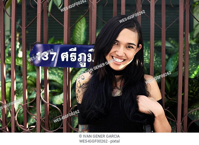 Portrait of a happy tattooed woman at garden fence