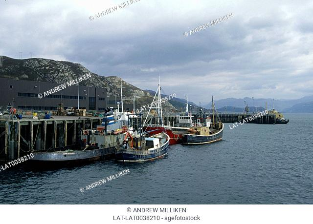 Harbour. Four fishing boats with masts and winches. Quay. Fishboxes. Forklift truck. Sea