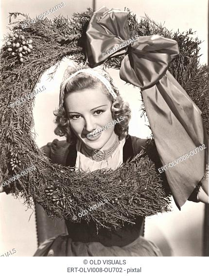 Woman holding large Christmas wreath with bow
