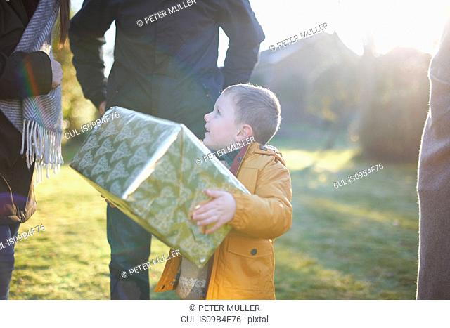 Happy boy carrying present with family in garden