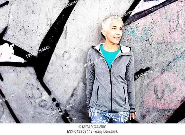 Senior Woman Relax After Running, Leaning On The Gray Concrete Wall. Short Hair, Sports Clothes , Looking At The Side