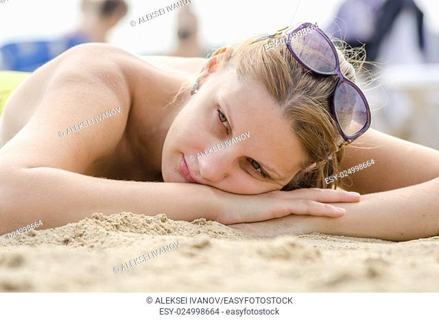 Sad young girl lying on sandy beach and looking to the side