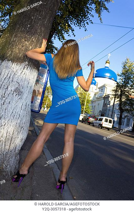 Beautiful, attractive Ukrainian woman wearing a blue dress lying on a tree and calling a taxi near the Orthodox Cathedral of St Michael to a photographic...
