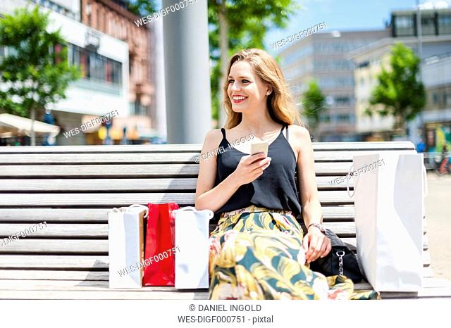 Portrait of smiling young woman sitting on a bench with shopping bags holding smartphone