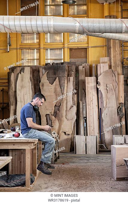 Caucasian man factory worker taking a break checking phone messages in a woodworking factory