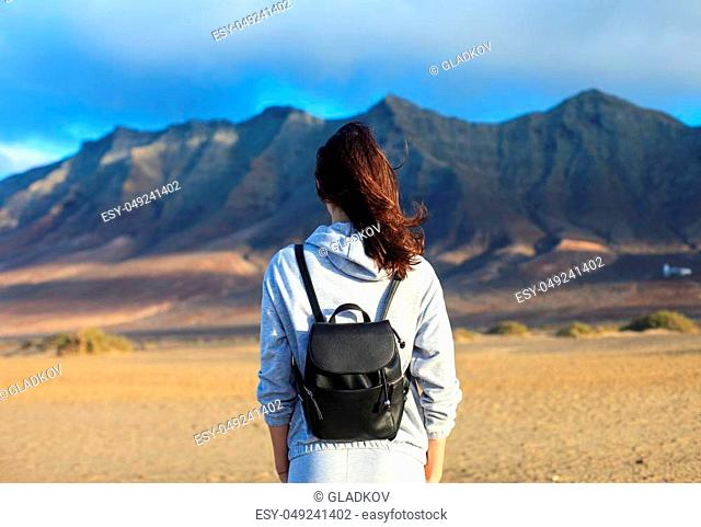 Back view of traveler woman enjoying beautiful mountains landscape. Canary islands, Spain. Tourism concept