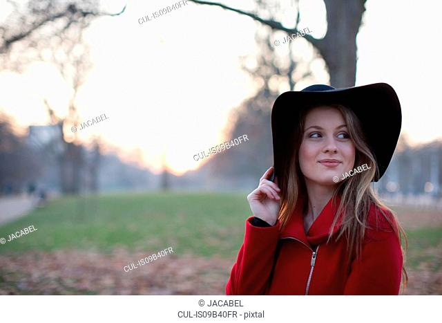 Young woman in floppy hat in park, London, UK
