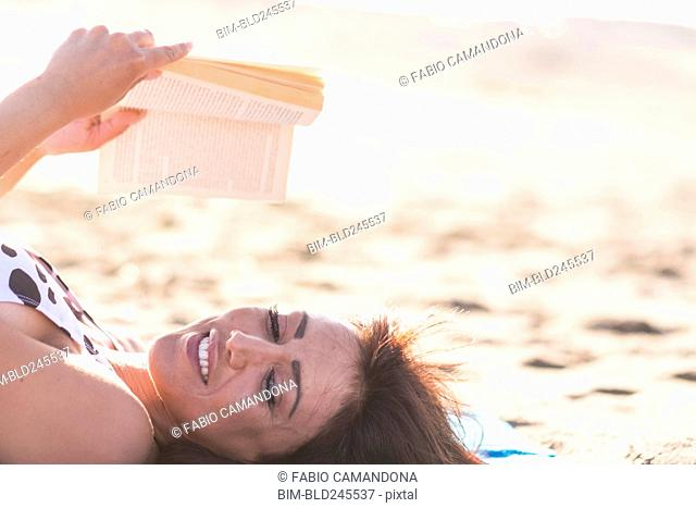 Caucasian woman laying on beach reading book