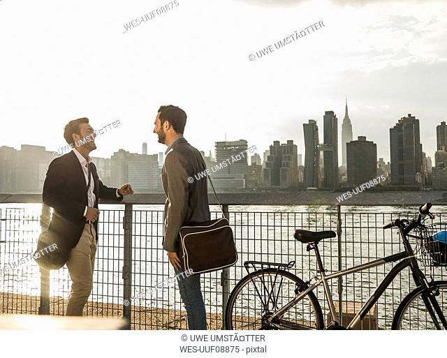 USA, New York City, two businessmen with bicycle at East River